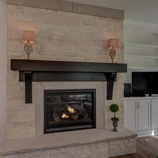 Offenes Rustikales Wohnzimmer mit grauer Wandfarbe, braunem Holzboden, Kamin, gefliestem Kaminsims, Eck-TV und braunem Boden in Indianapolis