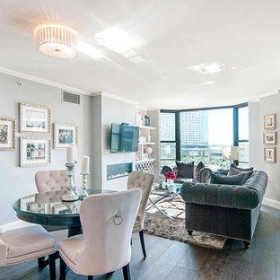Modelo de sala de estar abierta, minimalista, pequeña, con paredes grises, suelo de madera oscura, chimenea tradicional y televisor colgado en la pared