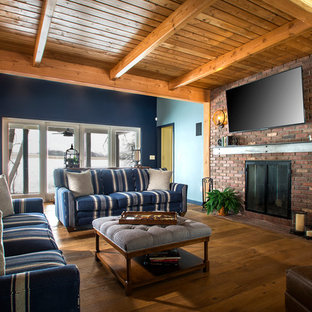 Family room - rustic medium tone wood floor and brown floor family room idea in New York with a brick fireplace, blue walls, a standard fireplace and a wall-mounted tv
