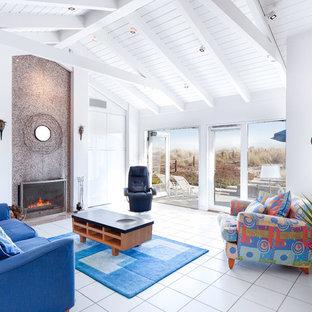 サンフランシスコの大きいビーチスタイルのおしゃれなファミリールーム (白い壁、磁器タイルの床、標準型暖炉、石材の暖炉まわり、白い床) の写真