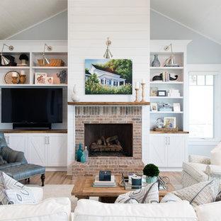 Idee per un soggiorno costiero aperto con pareti blu, parquet chiaro, camino classico, cornice del camino in mattoni e parete attrezzata