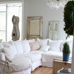 Idée de décoration pour une salle de séjour style shabby chic avec un mur gris et un sol en bois brun.