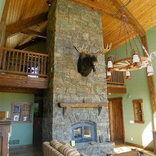 Idées déco pour une salle de séjour mansardée ou avec mezzanine montagne de taille moyenne avec un sol en bois brun, une cheminée standard, un manteau de cheminée en pierre, un mur vert et aucun téléviseur.