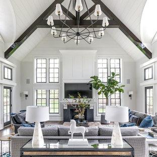 Diseño de sala de estar abierta, tradicional renovada, grande, con paredes blancas, suelo de madera en tonos medios, chimenea tradicional, televisor colgado en la pared y suelo marrón