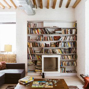 ニューヨークの中サイズのインダストリアルスタイルのおしゃれなファミリールーム (ライブラリー、白い壁、淡色無垢フローリング、標準型暖炉、テレビなし) の写真