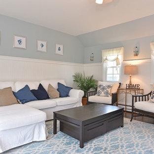 プロビデンスの広いビーチスタイルのおしゃれな独立型ファミリールーム (青い壁、無垢フローリング、標準型暖炉、レンガの暖炉まわり、壁掛け型テレビ、黒い床) の写真