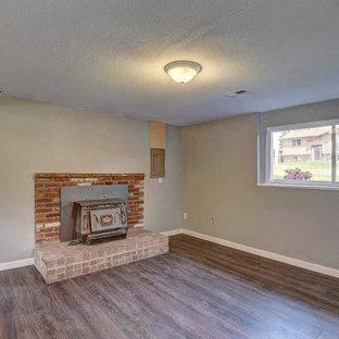 シアトルの大きいコンテンポラリースタイルのおしゃれなファミリールーム (グレーの壁、ラミネートの床、薪ストーブ、レンガの暖炉まわり、テレビなし、グレーの床) の写真