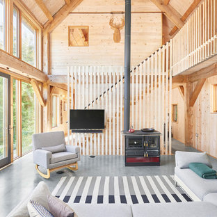 Mountain style open concept gray floor family room photo in Boston with a wood stove, a metal fireplace and a wall-mounted tv