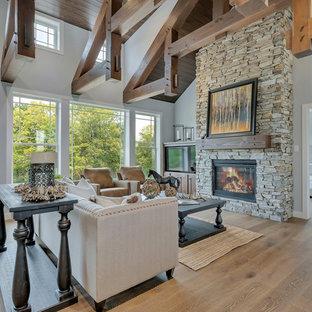 ミネアポリスの中サイズのおしゃれなファミリールーム (グレーの壁、無垢フローリング、標準型暖炉、石材の暖炉まわり、コーナー型テレビ、茶色い床) の写真
