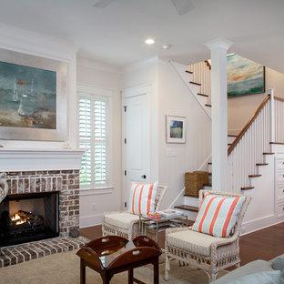 チャールストンの中サイズのビーチスタイルのおしゃれなファミリールーム (白い壁、標準型暖炉、レンガの暖炉まわり、無垢フローリング) の写真