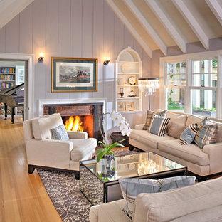 Idee per un soggiorno country con pareti viola, pavimento in legno massello medio, camino classico, cornice del camino in mattoni e pavimento marrone