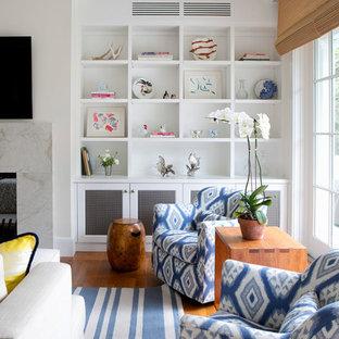 Idées déco pour une grande salle de séjour bord de mer avec un mur beige, un sol en bois brun, une cheminée double-face, un manteau de cheminée en pierre et un téléviseur fixé au mur.