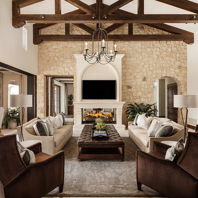 Family room - large mediterranean open concept travertine floor and beige floor family room idea in Phoenix with white walls, a two-sided fireplace, a wall-mounted tv and a stone fireplace