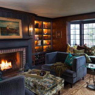 Ejemplo de sala de estar con biblioteca cerrada, clásica, pequeña, con paredes marrones, suelo de madera oscura, chimenea tradicional, marco de chimenea de ladrillo y suelo marrón