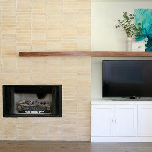 ラスベガスの大きいエクレクティックスタイルのおしゃれなファミリールーム (白い壁、淡色無垢フローリング、標準型暖炉、レンガの暖炉まわり、埋込式メディアウォール、ベージュの床) の写真