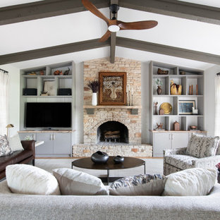 Transitional open concept medium tone wood floor, brown floor, exposed beam and vaulted ceiling family room photo in Austin with gray walls, a standard fireplace, a stone fireplace and a media wall