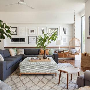 Ispirazione per un grande soggiorno stile marino aperto con pareti bianche, pavimento in legno massello medio, camino classico, cornice del camino in intonaco e TV a parete