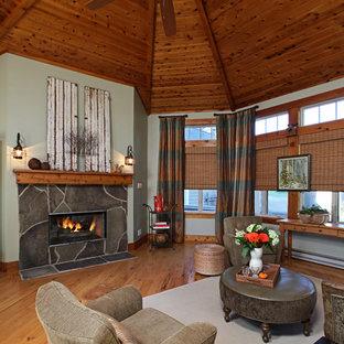 デトロイトの広いトラディショナルスタイルのおしゃれなオープンリビング (緑の壁、無垢フローリング、両方向型暖炉、石材の暖炉まわり、テレビなし) の写真