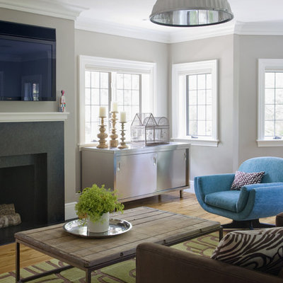 Elegant medium tone wood floor family room photo in Boston with gray walls and a wall-mounted tv