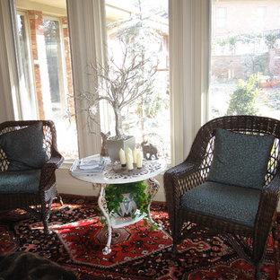 Foto de sala de estar con biblioteca cerrada, bohemia, pequeña, con paredes beige, suelo de madera en tonos medios, chimenea tradicional, marco de chimenea de piedra y pared multimedia
