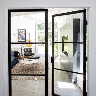 Foto de sala de estar con rincón musical cerrada, vintage, de tamaño medio, sin chimenea, con paredes blancas, suelo de cemento, suelo gris y pared multimedia