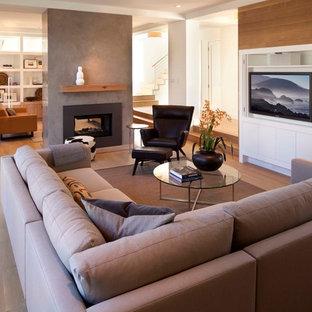 Idée de décoration pour une salle de séjour design ouverte avec un sol en bois brun, une cheminée double-face et un téléviseur encastré.