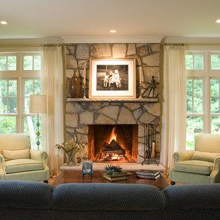 Diseño de sala de estar cerrada, clásica, grande, con marco de chimenea de piedra, paredes beige, suelo de madera en tonos medios, chimenea tradicional y suelo marrón