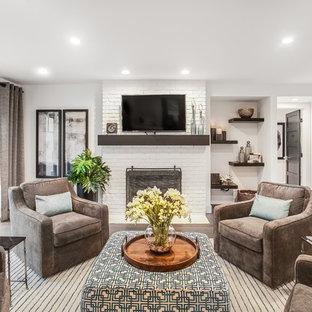 グランドラピッズのコンテンポラリースタイルのおしゃれなオープンリビング (白い壁、無垢フローリング、薪ストーブ、レンガの暖炉まわり、壁掛け型テレビ、茶色い床) の写真