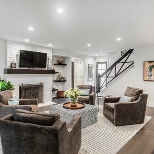 グランドラピッズのコンテンポラリースタイルのおしゃれなファミリールーム (白い壁、無垢フローリング、薪ストーブ、レンガの暖炉まわり、壁掛け型テレビ、茶色い床) の写真