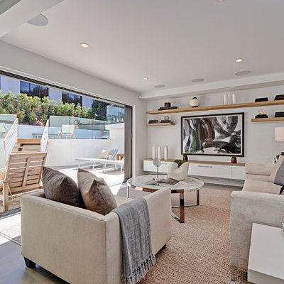 Mid-sized trendy open concept light wood floor family room photo in Los Angeles with a bar, white walls and a wall-mounted tv