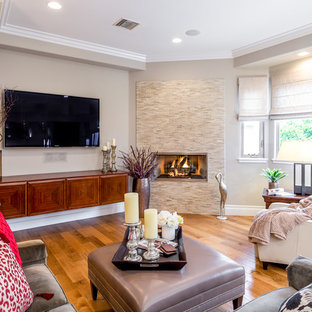 Example of a mid-sized transitional open concept medium tone wood floor and brown floor family room design in Los Angeles with a wall-mounted tv, beige walls, a hanging fireplace and a tile fireplace