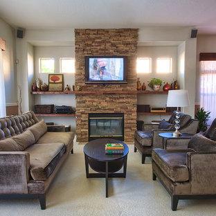 フェニックスの中サイズのコンテンポラリースタイルのおしゃれなファミリールーム (標準型暖炉、石材の暖炉まわり、壁掛け型テレビ、ベージュの壁、カーペット敷き) の写真