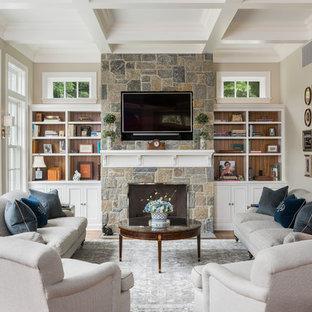 Esempio di un soggiorno chic con libreria, pareti beige, camino classico, cornice del camino in pietra e TV a parete