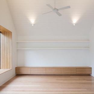 Diseño de sala de estar cerrada, escandinava, de tamaño medio, con paredes blancas, suelo de madera clara, televisor independiente y suelo beige