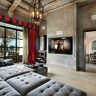Idée de décoration pour une salle de séjour méditerranéenne avec un mur gris, un sol en bois clair et un téléviseur fixé au mur.