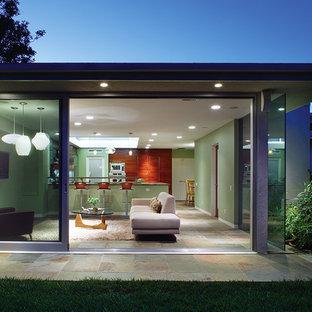 Aménagement d'une salle de séjour contemporaine ouverte et de taille moyenne avec un mur vert et un sol en ardoise.