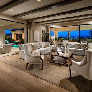 Idée de décoration pour une grande salle de séjour méditerranéenne ouverte avec un mur beige, un sol en bois clair, une cheminée ribbon, un manteau de cheminée en pierre et un téléviseur fixé au mur.