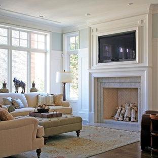 シカゴの中サイズのトラディショナルスタイルのおしゃれなファミリールーム (グレーの壁、無垢フローリング、標準型暖炉、タイルの暖炉まわり、埋込式メディアウォール、茶色い床) の写真