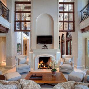 Idee per un grande soggiorno classico aperto con TV a parete, pareti beige, pavimento in pietra calcarea, camino classico, cornice del camino in pietra e pavimento beige