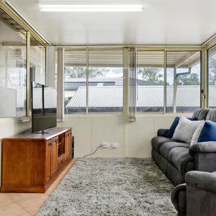 シドニーの中サイズのコンテンポラリースタイルのおしゃれな独立型ファミリールーム (ライブラリー、ベージュの壁、テラコッタタイルの床、暖炉なし、据え置き型テレビ、ピンクの床) の写真
