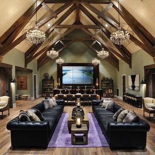 Immagine di un soggiorno country aperto con angolo bar, pavimento in legno massello medio, TV a parete e pareti verdi