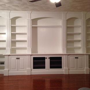 Cette photo montre une grande salle de séjour craftsman fermée avec un mur blanc, un sol en bois brun et un téléviseur encastré.