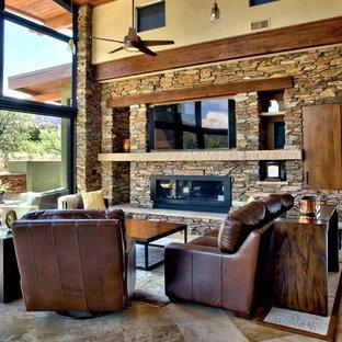 フェニックスの大きいサンタフェスタイルのおしゃれなオープンリビング (茶色い壁、標準型暖炉、石材の暖炉まわり、埋込式メディアウォール、トラバーチンの床) の写真
