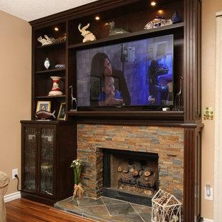 オレンジカウンティの小さいトロピカルスタイルのおしゃれなファミリールーム (ゲームルーム、ベージュの壁、無垢フローリング、標準型暖炉、壁掛け型テレビ、石材の暖炉まわり) の写真