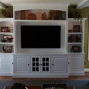 Aménagement d'une grande salle de séjour classique ouverte avec un mur vert, aucune cheminée, un téléviseur encastré et un sol marron.