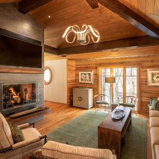 Foto de sala de estar abierta, rural, con paredes marrones, suelo de madera en tonos medios, chimenea tradicional, marco de chimenea de baldosas y/o azulejos y suelo marrón