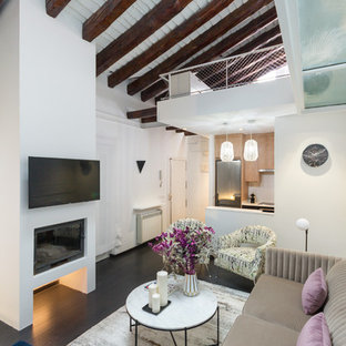 Ejemplo de sala de estar abierta, industrial, con paredes blancas, suelo de madera oscura, chimenea lineal y televisor colgado en la pared