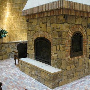 Foto di un grande soggiorno stile rurale con pareti beige, pavimento in mattoni, camino classico e cornice del camino in pietra