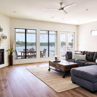 他の地域のビーチスタイルのおしゃれなファミリールーム (白い壁、無垢フローリング、コーナー設置型暖炉) の写真