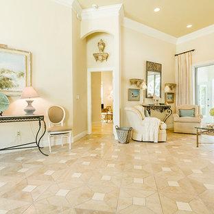 Immagine di un ampio soggiorno tropicale aperto con pareti beige, pavimento in pietra calcarea, nessun camino e cornice del camino in cemento
